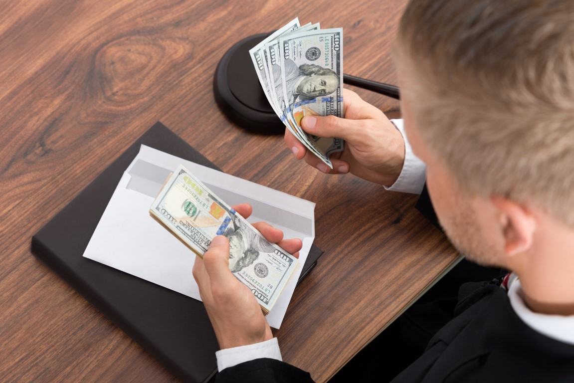 Close-up Of Lawyer Counting Money At Desk In Courtroom