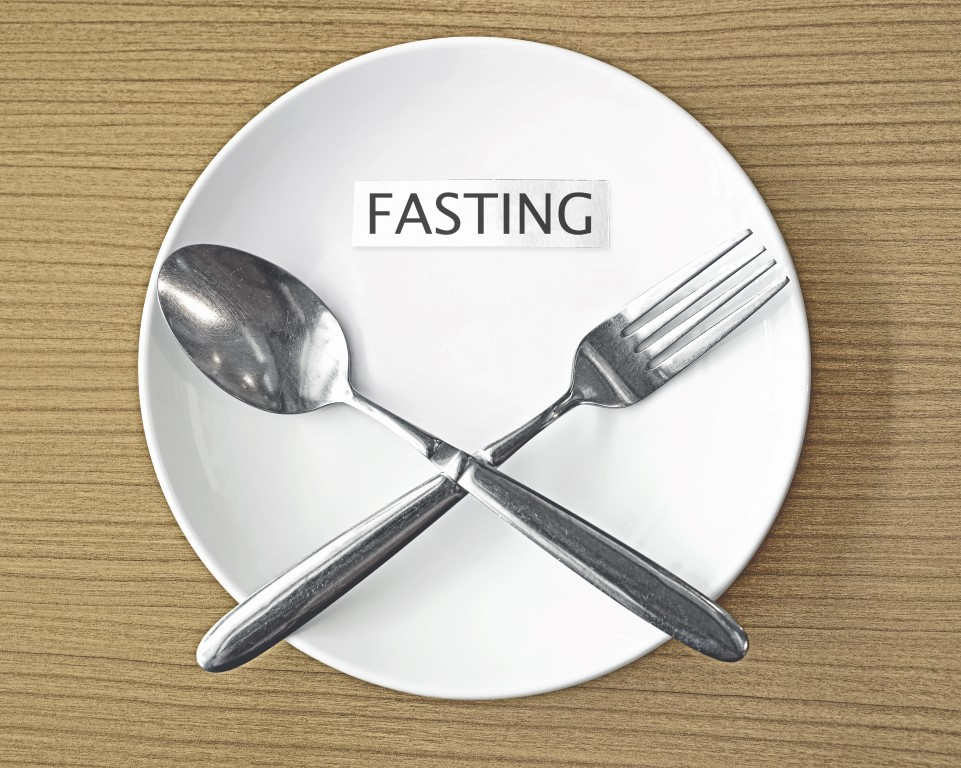 fasting paper and fork with spoon symbol on white plate